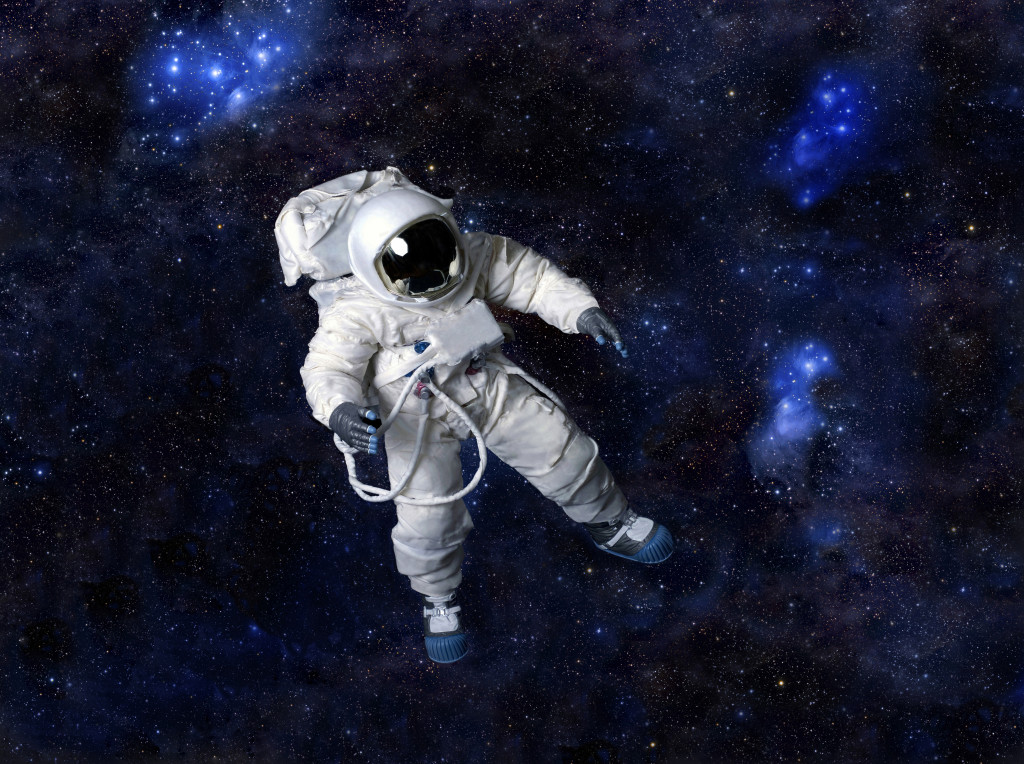 Astronaut wearing pressure suit against a space background.
